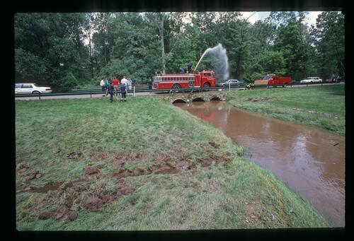 Firemen draining the overflowing rain water at the 1989 US Open Championship at Oak Hill