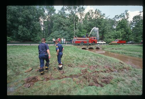 Firemen assessing the water saturation of the grounds at the 1989 US Open Championship