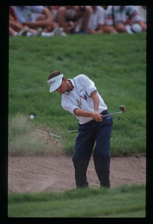 A golfer blasts out of a greenside bunker at the 91st United States Open Championship