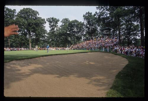 The crowds react to the putt as it hits the hole at the United States Open Championship