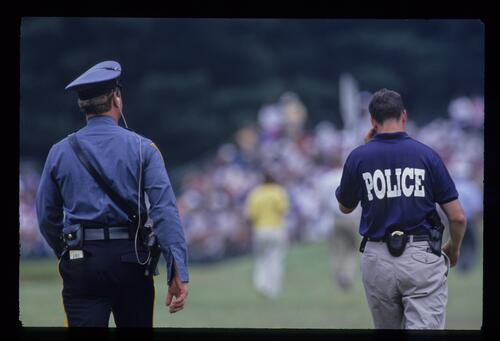 Police Officers follow the action at the United States Open Championship