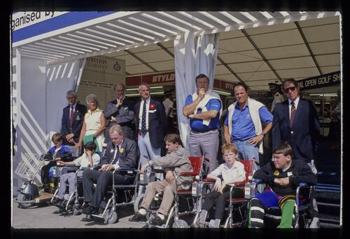 Peter Alliss and photographer Lawrence Levy pose with the 1990 group of recipients of donated powered wheelchairs at the 1990 Open Championship