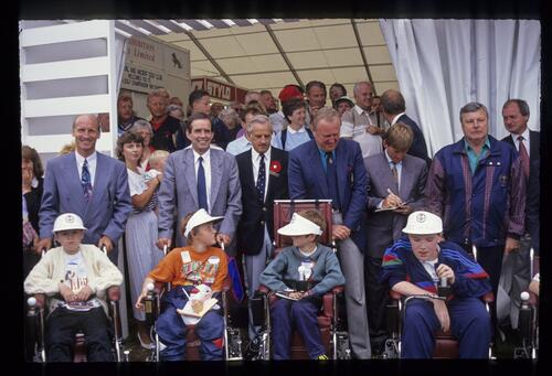 A group of recipients of electric wheelchairs from the Peter Alliss Charity at the 1992 Open Championship