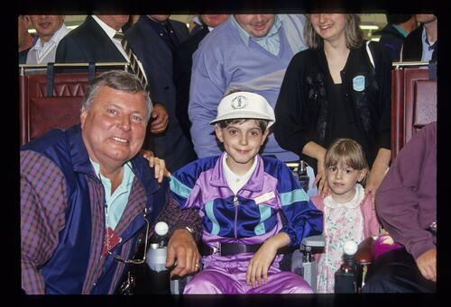 Peter Alliss poses with a recipient of a new powered wheelchair at the 1993 Open Championship