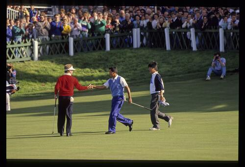 Japan's Koichi Suzuki shakes hands with the American golfer Tom Kite on the 18th green as they halve the match in the final of the 1989 Dunhill Cup