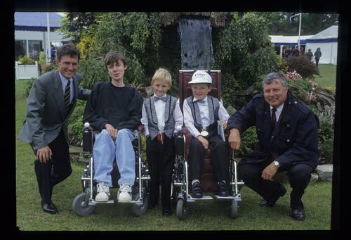 Peter Alliss poses with recipients of powered wheelchairs at the Volvo British PGA Championship at Wentworth