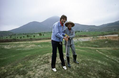 A golfer shows a Chinese labourer how to hold the golf club at the Chung Shan Hot Spring Golf Club