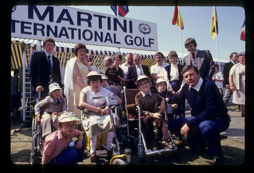 Peter Alliss poses with the recipients of new powered wheelchairs at the Martini International Golf Championship