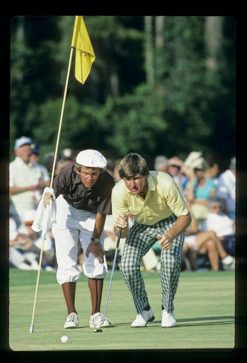 Golfer Nick Faldo lines up his putt with the help of his caddie at the Walt Disney World Classic Golf Tournament