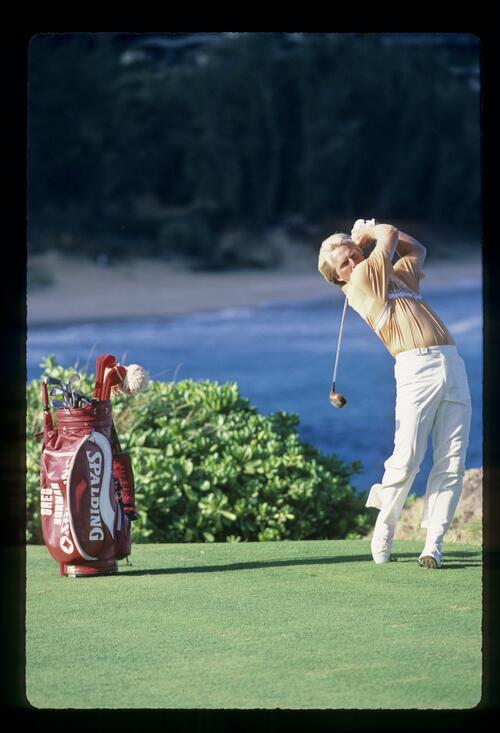 Greg Norman on the follow-through from the tee at the Kapalua International Golf Championship