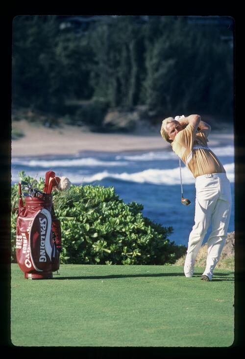 Greg Norman completes his swing on the tee at the Kapalua Internatioanl Golf Championship