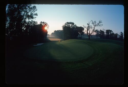 The early morning sun highlights the pin at the Muirfield Village Golf Course
