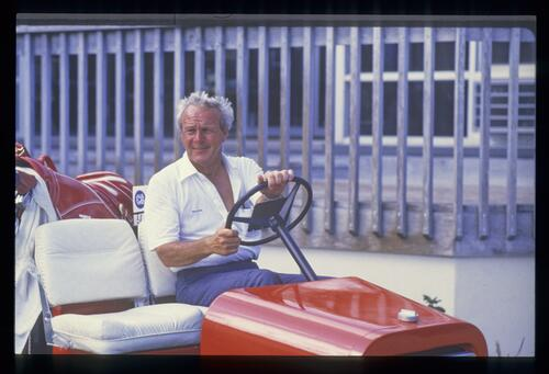 Arnold Palmer behind the wheel of his replica tractor golf cart at Bay Hill