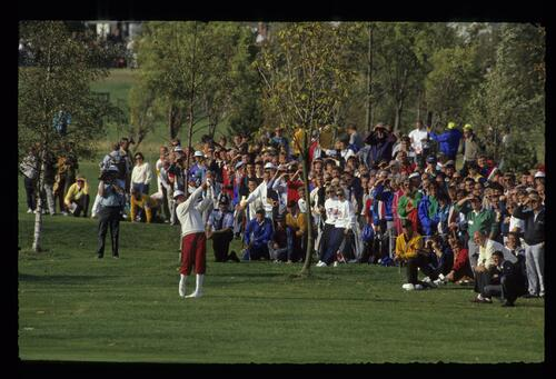 The crowds watch as American golfer Payner Stewart plays his fairway shot at the 1989 Ryder Cup