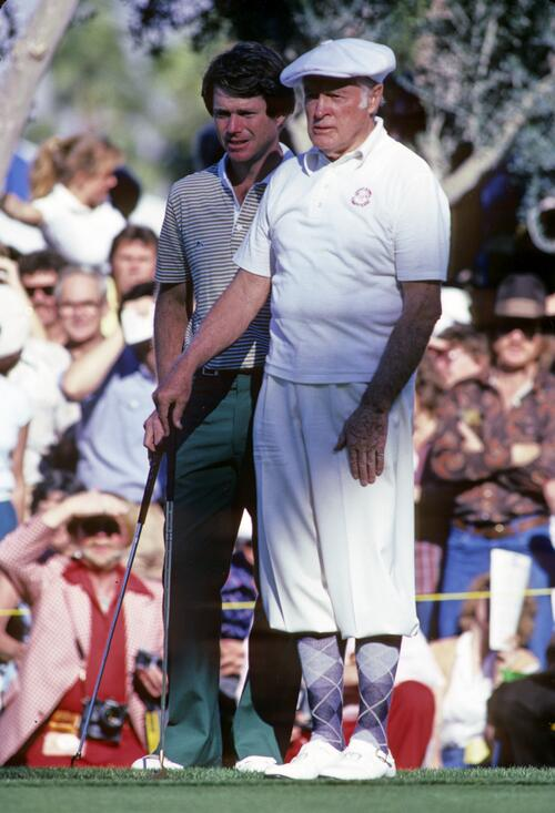 Actor and tournament sponsor Bob Hope waits on the green with golfer Tom Watson at the Bob Hope Desert Classic Golf Tournamenrt