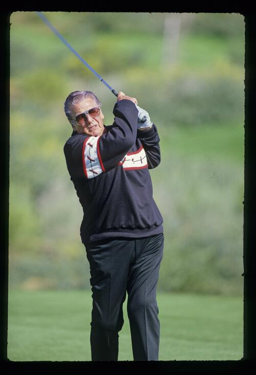 Actor Victor Mature tees off at the 1987 Bob Hope Chrysler Classic GolF Championship