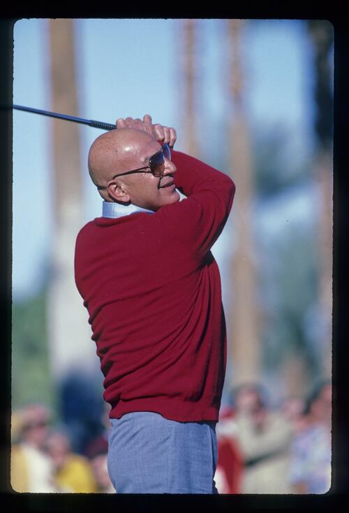 Telly Savalas tees off at the 1982 Bob Hope Desert Classic Golf Championship