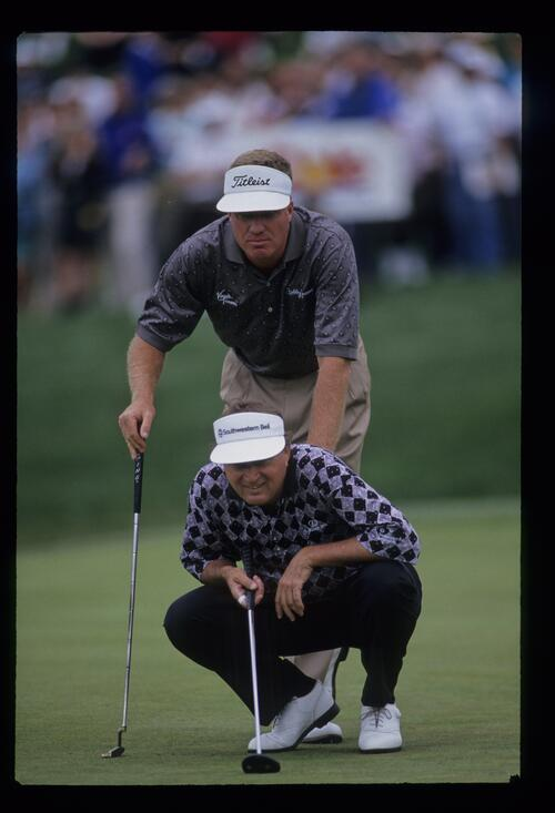 Teammates Ray Floyd and Steve Elkington line up the putt on the way to victory at the 1993 Shark Shootout