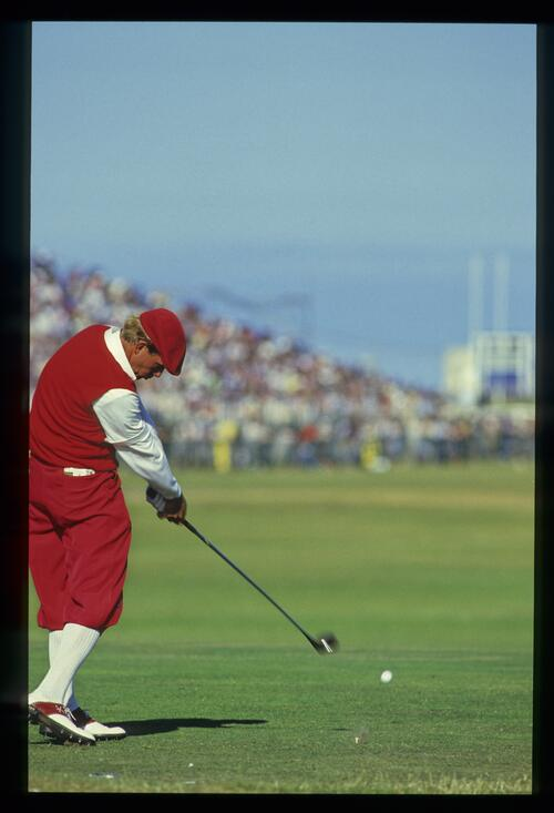 American golfer Payne Stewart, dressed in red Plus-Fours, tees off at The Open Championship at St Andrews