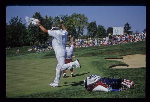 American golfer Tom Kite and his caddie celebrate his win over opponent Sandy Lyle at the 1987 Ryder Cup