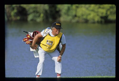 A caddie checks the line of his golfer's putt at the Bay Hill Classic