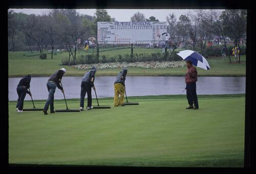 The greenkeepers busy clearing the rainwater from the greens at the 1991 Nestle Invitational at bay Hill