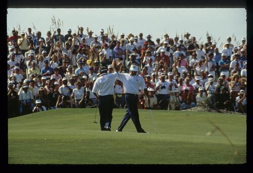 American teammates Lanny Wadkins and Mark O'Meara give high-5s as they halve the match with Sam Torrance and David Feherty on Day 1 on the 1991 Ryder Cup