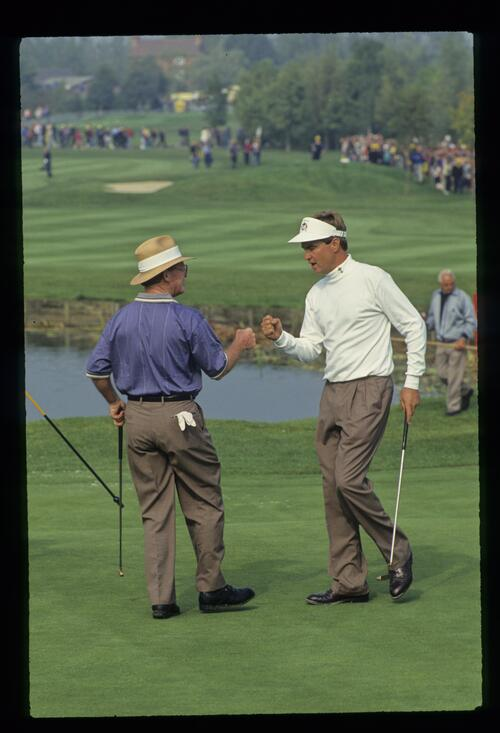 Teammates Tom Kite and Davis Love III bump fists as they claim a victory over Europe's Seve Ballesteros and Jose Maria Olazabal at the 1993 Ryder Cup
