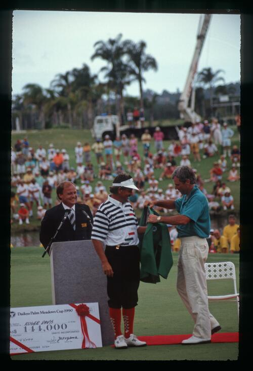A victorious Rodger Davis dons the green jacket with the help of Curtis Strange at the 1990 Daikyo Palm Meadows Cup Championship