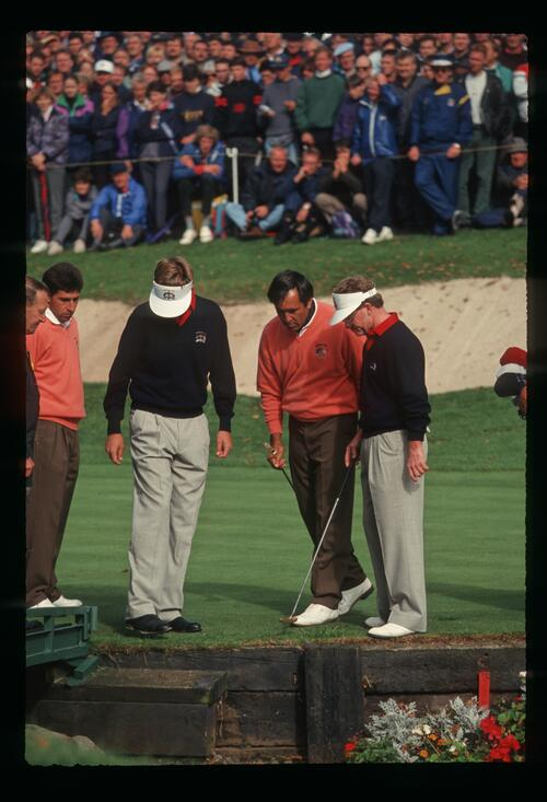 The two opposing teams look for Davis Love III's ball as it skirted across the green from his bunker shot to the water on the 10th hole at the 1993 Ryder Cup