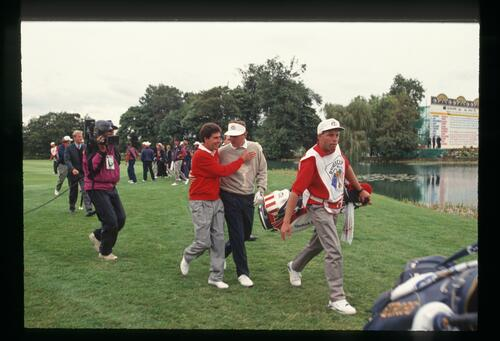 Opponents Jose Maria Olazabal and Ray Floyd are in good spirits when Olazabal concedes the match as they approach the 18th green on the final day of the 1993 Ryder Cup