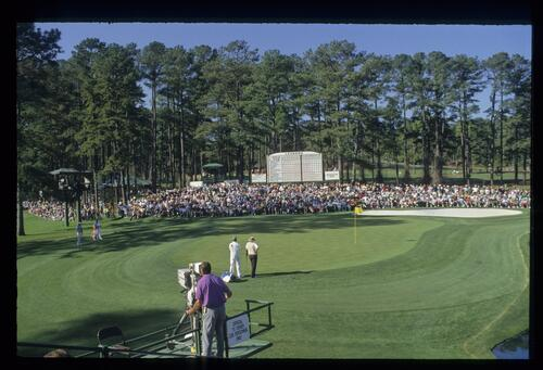 A TV cameraman focuses on Ray Floyd chipping to the 15th green as Russ Cochran watches during the 1993 Masters