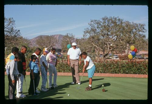 Professional golfer Ray Floyd helps a group of youngsters with their putting at the 1990 Ronald McDonald Children's Charity Golf Tournament