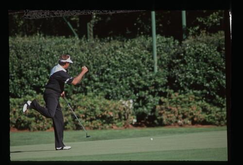 Golfer Ray Floyd gives a skip in his step as he holes his putt at the 1990 Masters Championship