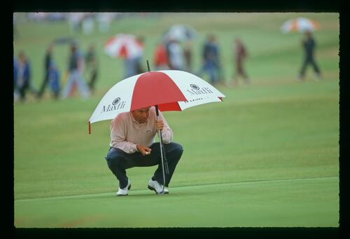 Golfer Ray Floyd peers out from under his umbrella on the green at the 1987 Open Championship at Muirfield