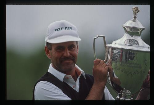A victorious Mark James lifts the trophy after winning the 1990 NM English Open Championship at The Belfry