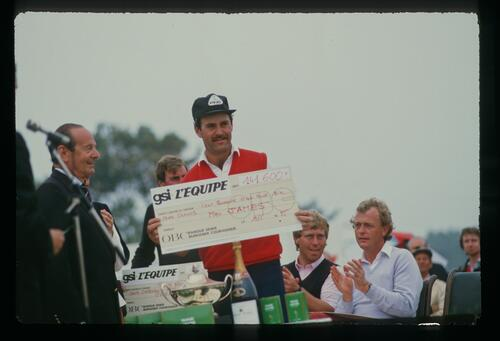English golfer Mark James accepts the winner's cheque at the 1985 GSI-L'Equipe Open Championship in France