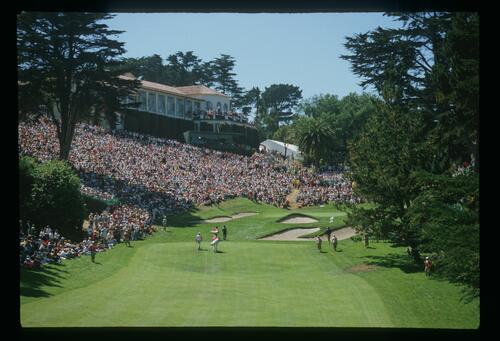 Golfers climbing to the 18th green and an amphitheatre of fans during the 1987 US Open