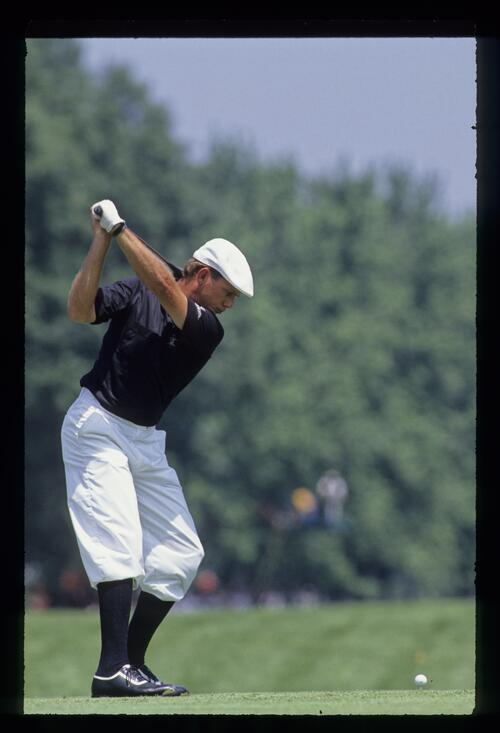 Payne Stewart, in the colours of the Oakland Raiders, at the top of his backswing while driving at the 1990 US Open