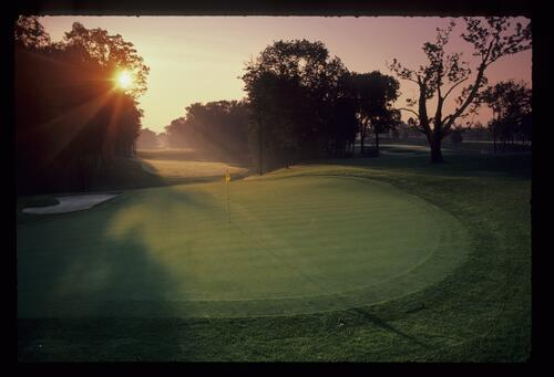The early morning sun rising over a green at Muirfield Village