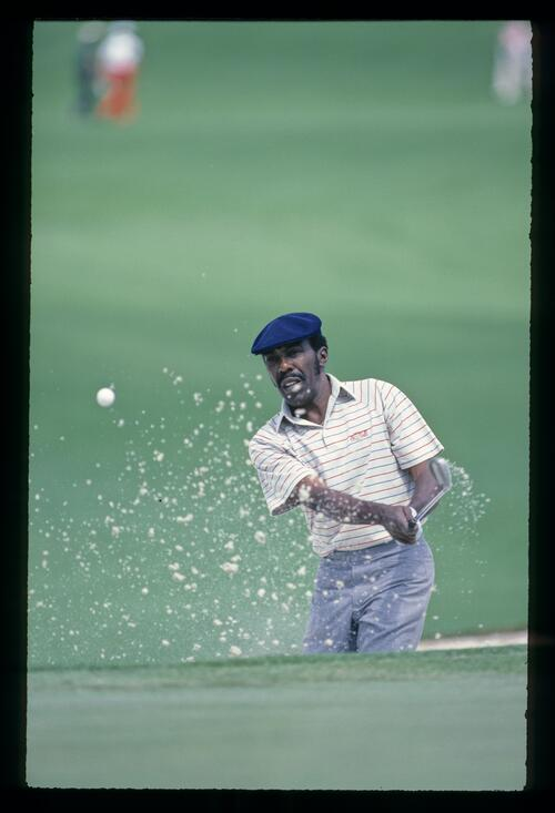Calvin Peete blasts out of the greenside bunker at the 1985 Masters Championship at Augusta