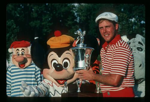 Golfer Payne Stewart lifts the winner's trophy at the 1983 Walt Disney World Classic