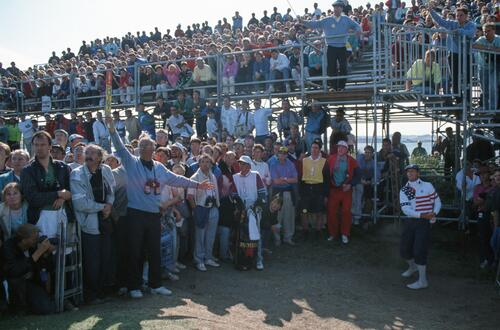 Marshals hold back the spectators as golfer Payne Stewart plays his shot from beneath the stands at the 1990 Open Championship at St Andrews