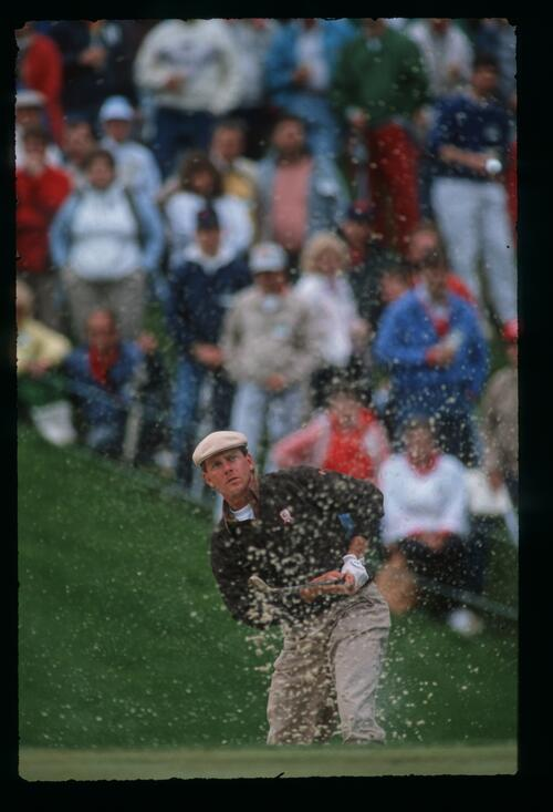 Golfer Payne Stewart blasts his ball out of the greenside bunker at the 1989 Memorial Tournament