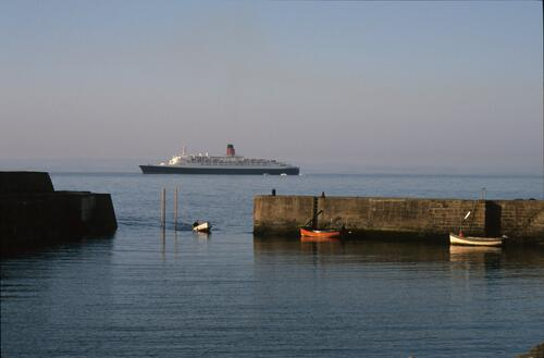 The QE2 (Queen Elizabeth II) out at sea beyond Cellardyke harbour.