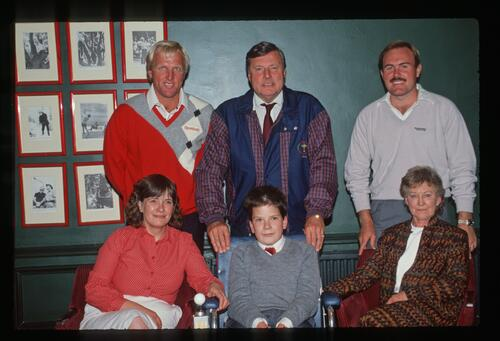 Greg Norman, Peter Alliss and Rnan Rafferty pose with a new recipient of a powered wheelchair and his family at the 1989 Dunhill Cup at St Andrews