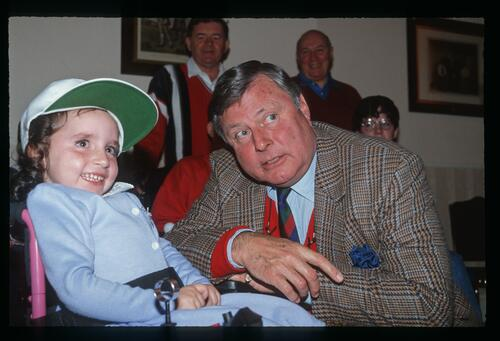 Peter Alliss poses with a young recipient of a new powered wheelchair
