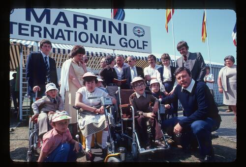Peter Alliss poses with the newst group of recipients of powered Wheelchairs at the 1982 Martini International Golf Tournament