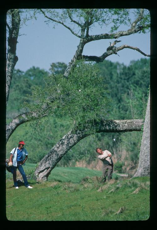 Golfer Lanny Wadkins plays his shot over the trees at the 1984 Players Championship at Sawgrass