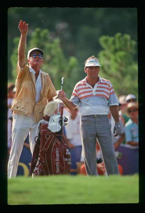 Golfer Lanny wadkins makes his club selection while his caddie tests the wind direction at the 1987 U. S. PGA Championship